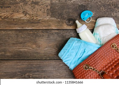 Women's handbag with items to care for the child on old wooden background