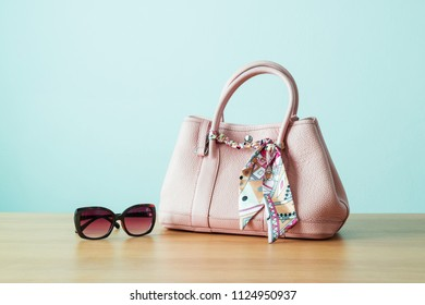 Women's handbag and sunglasses for ladies style or working women on wooden table