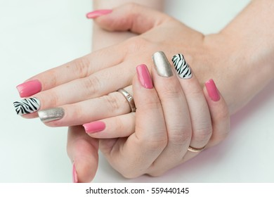 Women's hands with a cheerful manicure closeup on a white background. nail design pink and silver zebra style