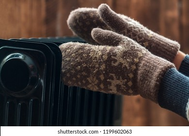 Women's hands in Christmas, warm, winter mittens on the heater. Keep warm in the winter, cold evenings