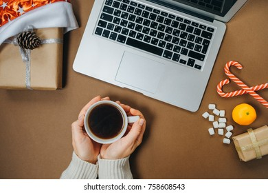 Women's hands with Coffee and marshmallows on Christmas background with Laptop and gifts on brown table. Top view, flat lay