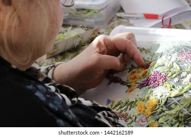 Women's hands embroidering a picture which depicts meadow grass and flowers. The picture is embroidered with ribbons