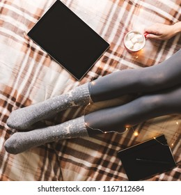 Women's hands and feet in sweater and woolen cozy gray socks holding cup of hot coffee, sitting on plaid with garland, tablet and notebook. Concept winter comfort. Square format for social networks