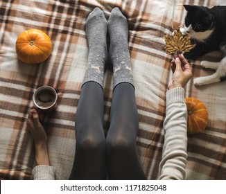 Women's hands and feet in sweater and woolen cozy gray socks holding cup of hot coffee, sitting on plaid with kitten, pumpkin, candles and leaves. Concept winter comfort, morning drinking.
