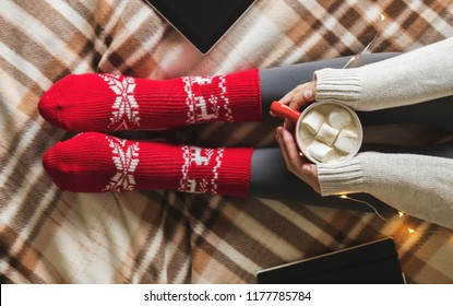 Women's hands and feet in sweater and woolen cozy red socks holding cup of hot coffee with marshmallow, sitting on plaid with garland, tablet and notebook. Concept winter comfort, morning drinking
