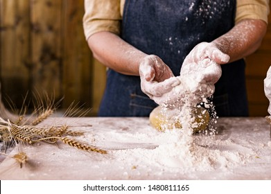 Women's hands, flour and dough. Levitation in a frame of dough and flour. A woman in an apron is preparing dough for home baking. Rustic style photo. Wooden table, wheat ears and flou.Emotional photo