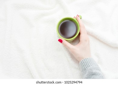 women's hands, girl holding a Cup of coffee, lying on the blanket, white background with copy space, for advertising, top view