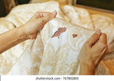 Women's hands hold bed sheet with period blood spot stains on blur background. Need to be cleaning.
