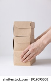 women's hands hold cardboard boxes, natural color, eco-friendly and biodegradable products, boxes for the delivery of food and gifts, confectionery and food