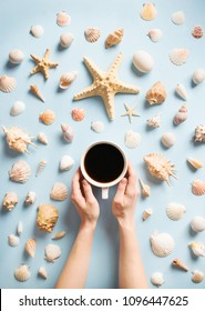 Women's hands hold a cup of coffee on a blue summer background with different shells and starfish. Sea marine holiday instagram flat lay. Vacation background. Top view.