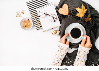 Women's hands hold a cup of coffee  wrapped in scarf  on a warm plaid. Autumn or Winter concept.  flat lay, top view
