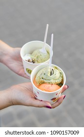 Women's hands hold paper cup with ice cream. Ice cream pistachios and mango