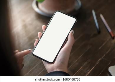 Händchen von Frauen, die ein Handy mit einem leeren Kopienraum-Bildschirm halten. Smartphone mit Technologiekonzept