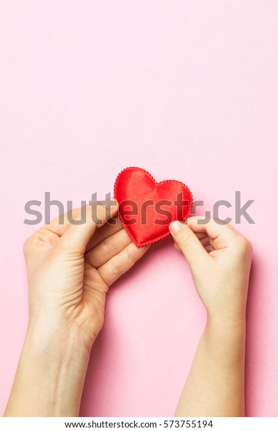 Women's hands holding the child's hand with a heart. The concept of motherhood, caring, family, protection, love. Place for text. Flat fly