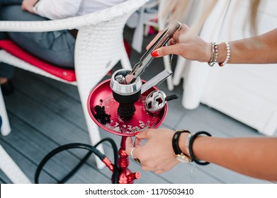 Womens hands holding forceps for shisha hookah and adjusts hot coals in metal bowl. Red hookah is standing on wooden floor in interior restaurant. Smoking Concept. Traditional Asian relaxation.