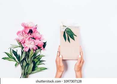 Women's hands holding a gift bag decorated with a silver bow and sprig, next to a bouquet of lush pink peonies, top view. Feminine flat lay composition with flowers and present on white background.