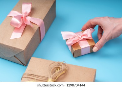 Women's hands holding gift box Packed in Kraft paper with pink ribbon on blue background. Concept holiday card for Valentine's day and women's day