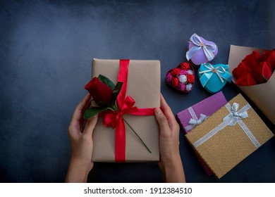Women's hands holding gift box made of Kraft paper with rose decor on a red ribbon. Concept of creating handmade gifts for Valentine's Day, New year, and Christmas. Top view and Holiday concept
