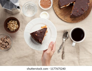 Women's hands holding a plate with piece of Peanut Butter Chocolate Caramel Cheesecake Pie. Top view of a Coffee Break concept with cup of coffee on dining table with linen tablecloth