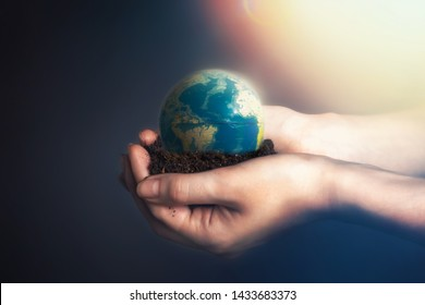 Women's hands holding soil with a globe of the planet Earth.The concept of environmental conservation, organic agriculture. Light from the top