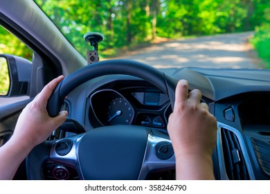 Women's hands holding the steering wheel of a vehicle