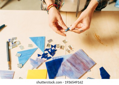 Women's hands holding tool for mosaic details in the process of making a mosaic