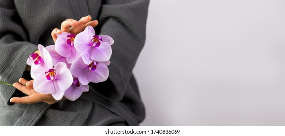 Women's hands with natural manicure holding branch of beautiful pink orchids. Beauty banner.