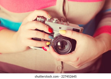 Women's hands with an old camera