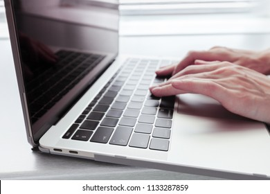 women's hands on a silver notebook MacBook Pro Retina in the case with USB Type-C on a grey table - June 28, 2018