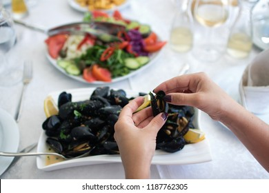 Women's hands open of boiled mussels served on the table. Albania. Adriatic coast. National food. Toned
