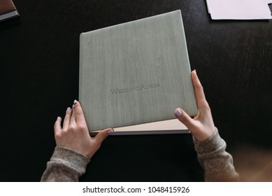 women's hands open the cover of a photobook that is light in color and lies on the table