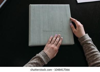 women s hands open the wedding album cover light eea9935331