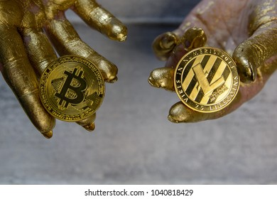 Women's hands painted with gold paint hold golden bitcoin and litecoin