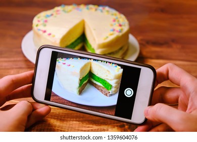 Women's hands with the phone taking pictures of the cake. Blogger shoots food for social network. Create a photo for posting on the Internet. White phone and a tri-color cake on a wooden table.