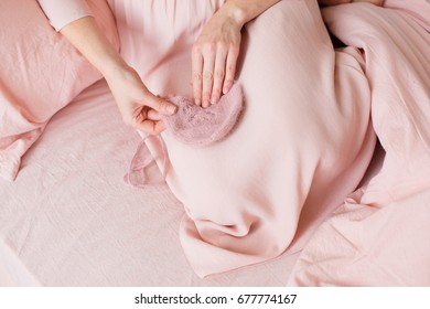 Women's hands with a pink children's hatMaternal carebaby clothes