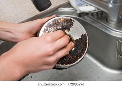 Women's hands to polish burned pot