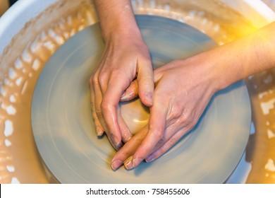 womens hands of a potter creating an earthen jar