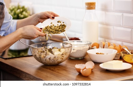 women's hands prepare dough with nuts and seeds for cookies in   kitchen