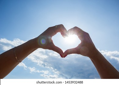 Women's hands in the shape of a heart against the sky miss the sun's rays. Hands in the form of hearts love