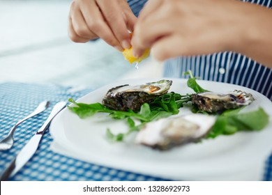 Women's hands squeezing lemon juice on raw oyster, close up. Platter of fresh raw oysters, green salad and lemon at an outdoor cafe