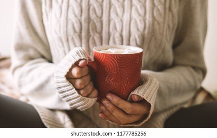 Women's hands in sweater are holding cup of hot coffee, chocolate or tea. Concept winter comfort, morning drinking, warm in middle of cold