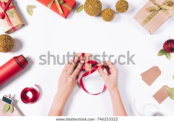 Women's hands are tied a red ribbon on Christmas gift top view