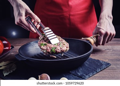 women's hands with tongs turn over a raw piece of beef with herbs in a cast iron pan.
