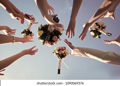 Women's hands trying catch four beautiful brides bouquets of roses pastel colors on clear blue sky background, horizontal photo