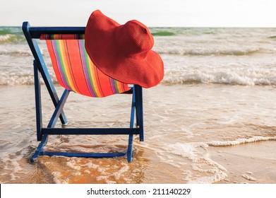 Women's hat on a beach chair on the beach