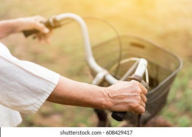 Women's Healthcare, older person hand holding bicycle