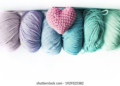 Women's hobby. Crochet and knitting.  Multicolored skeins  and pink knitted heart of yarn on a white background. Studio shooting.
