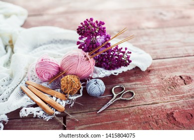 Women's hobby. Crochet and knitting. Working space. Pink balls of yarn, needles, scissors, crochet hooks on the wood table  in the cozy home.