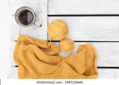 Women's hobby. Crochet and knitting. Working space.  Cup of coffee , balls of mustard yarn, needles, knitwear, crochet hooks on the wood table in the cozy home. flat lay/copy space