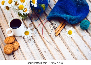Women's hobby. Crochet and knitting. Workspace. A bouquet of daisies in a vase, a white Cup with a drink, cookies, yarn balls, needles, scissors, knitwear, crochet hooks on a wooden table.